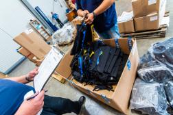 A megyei kollégák átveszik a hátizsákokat a raktárban.
